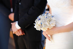 Bride holding flowers at the wedding ceremony Royalty Free Stock Photos