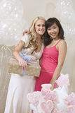 Bride Holding Gift While Standing With Friend Stock Photo