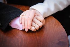 Bride holding the groom's hand on the table Stock Photos