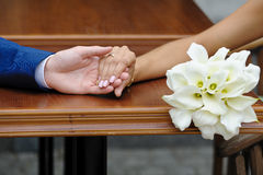 Bride holding the groom's hand and wedding bouquet Royalty Free Stock Image