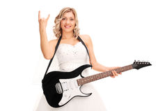 Bride holding guitar and making a rock gesture. Young bride holding a guitar and making a rock hand gesture isolated on white background Royalty Free Stock Images