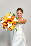 Bride holding her bouquet against a white wall Stock Images