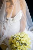 Bride holding her bouquet in lap Royalty Free Stock Photos