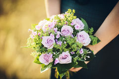 Bride holding her bouquet of purple flowers on her wedding day Stock Image