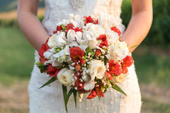 Bride holding her bouquet of red and white flowers Stock Images
