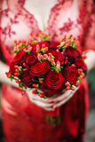 Bride holding her red wedding bouquet of flowers. Bride red lace dress is holding a round bouquet of red roses Royalty Free Stock Photography