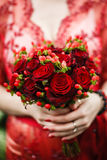 Bride holding her red wedding bouquet of flowers. Bride red lace dress is holding a round bouquet of red roses Royalty Free Stock Photo
