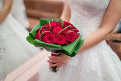 A bride holding her red wedding bouquet of flowers Royalty Free Stock Images