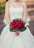 A bride holding her red wedding bouquet of flowers Royalty Free Stock Photo