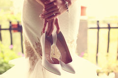 Bride holding her shoes Stock Photo