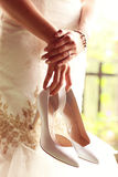 Bride holding her shoes Stock Images