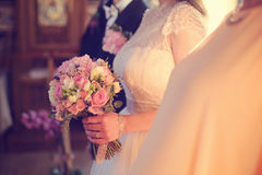 Bride holding her wedding bouquet in the church Stock Image