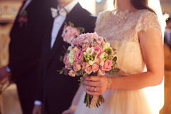 Bride holding her wedding bouquet in the church Royalty Free Stock Photos