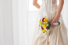 Bride holding her wedding flowers behind her back. A Beautiful bride holding her wedding flowers behind her back Royalty Free Stock Image