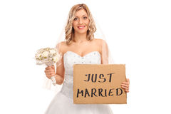 Bride holding a just married sign. Joyful bride holding a wedding flower and a banner that says just married isolated on white background Stock Image