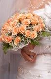 Bride holding orange bouquet detail Stock Photo