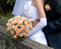 Bride holding orange bouquet detail Stock Images