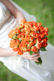 The bride holding orange wedding bouquet Stock Image