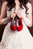 Bride holding a pair of red shoes Stock Images