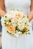 Bride Holding Peach Coral Rose Bouquet. A bride holding a fresh round bouquet of flowers with pink and coral peach roses in front of her dress Stock Image