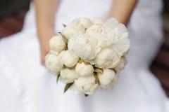 Bride holding peonies wedding bouquet