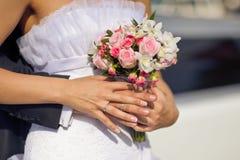 Bride holding pink wedding bouquet Stock Photos