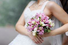 Bride holding pink wedding flowers bouquet. Bride holding beautiful pink wedding flowers bouquet Stock Photography