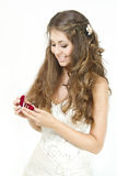 Bride holding red box with golden wedding rings. Bride holding red heart shaped box with two golden wedding rings. Smiling and looking at rings. Over white Royalty Free Stock Images
