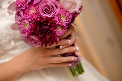 Bride holding a red flower bouquet Stock Images