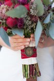 Bride holding red-and-green wedding bouquet Royalty Free Stock Photography