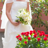 Bride holding red roses bouquet Stock Photo