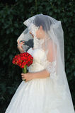 Bride holding red roses bouquet and bridal veil in hand Royalty Free Stock Photos