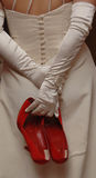 A bride holding Red Shoes. A bride holding her red wedding shoes behind her back royalty free stock photos