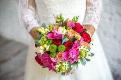 Bride holding rose pink wedding bouquet of roses and love flowers.  Stock Photo