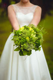 Bride holding rustical wedding bouquet Royalty Free Stock Photos