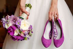 Bride holding shoes and colorful bouquet Stock Photos