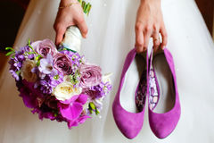 Bride holding shoes and colorful bouquet Royalty Free Stock Image