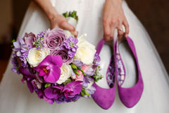 Bride holding shoes and colorful bouquet Royalty Free Stock Photos