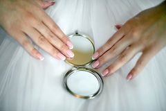 Bride holding a small mirror. Сloseup Royalty Free Stock Photo