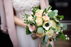 Bride holding stylish wedding flowers bouquet. Bride holding stylish wedding flowers. Elegance rustic style pastel colors bouquet in woman hands Stock Photography