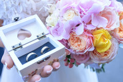 Bride holding a summer bouquet with pink hues and a small wooden box with the wedding bands for him and her. Stock Image