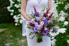 Bride holding a wedding bouquet close up Stock Images
