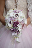 Bride holding wedding bouquet featuring calla lilies with purple accents and accessorized with silver jewelry. Vertical shot of bride dressed up in tulle dress Stock Photography