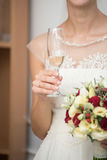 Bride is holding a wedding bouquet and a glass of champagne. Stock Images