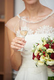 Bride is holding a wedding bouquet and a glass of champagne. Royalty Free Stock Photo