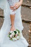 Bride is holding wedding bouquet in hands. Bride walks holding wedding bouquet in her hands Stock Photo