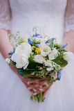 Bride holding a wedding bouquet in a park, close-up, Selective f Royalty Free Stock Image