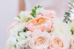 The bride is holding a wedding bouquet in pastel colors of peonies and roses stock photos