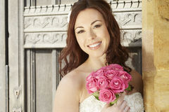 Bride holding a wedding bouquet of pink roses Stock Images