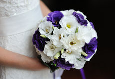 Bride holding wedding bouquet of purple flowers Stock Photography